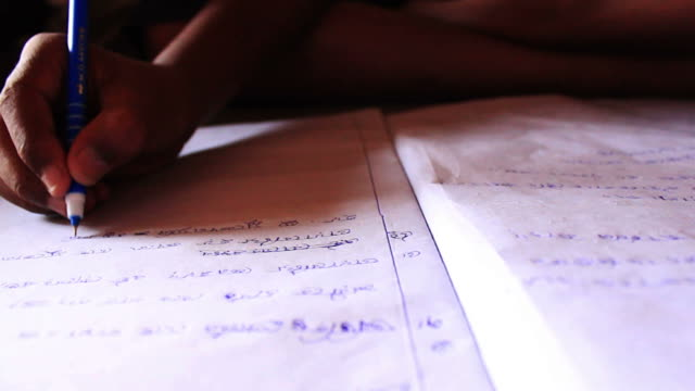 Closeup of a childs hand writing Bengali video