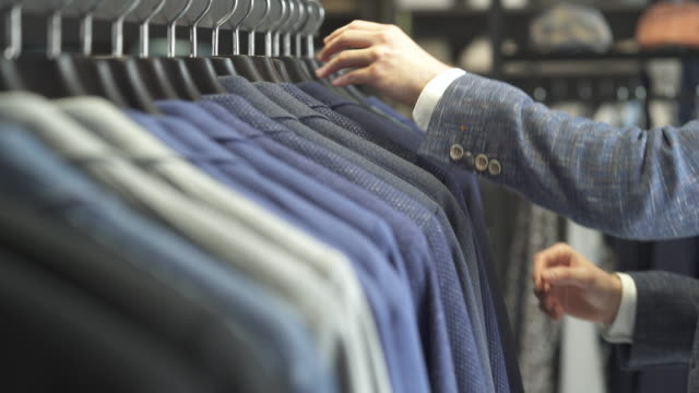 A close-up of a client looking through classic male suits in showroom of men business clothing shop. Boutique of brand male clothes video