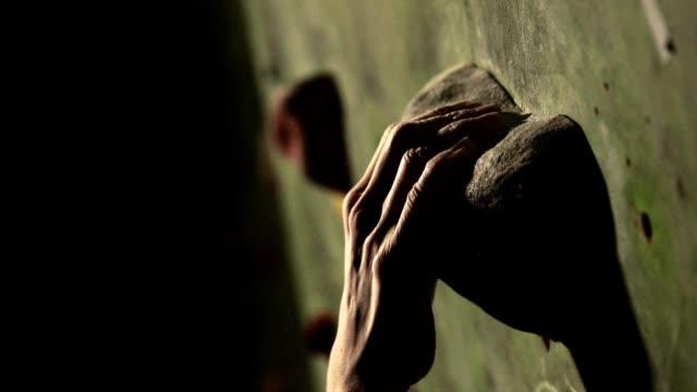 vídeos y material grabado en eventos de stock de primer plano de un escalador sube un muro de piedra en el interior. la escultura. la mano se fija en la meta. el ejercicio se completa - escalada en rocas