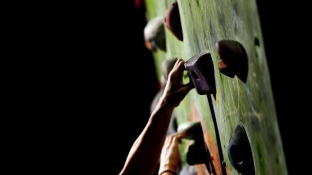 nahaufnahme eines kletterers klettert auf einer steinmauer im innenbereich. die skulptur. die hand ist am ziel fixiert. die übung ist abgeschlossen - bouldering stock-videos und b-roll-filmmaterial