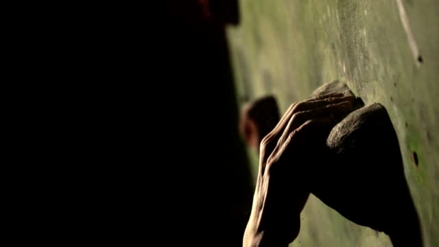 Close-up of a climbing wall, hand grasping a stone. Slow motion