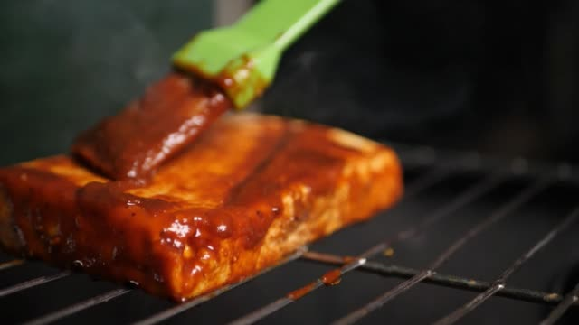 Closeup of a cottage cheese steak being barbecued on a grill with dramatic smoke and sauce being rubbing with brush