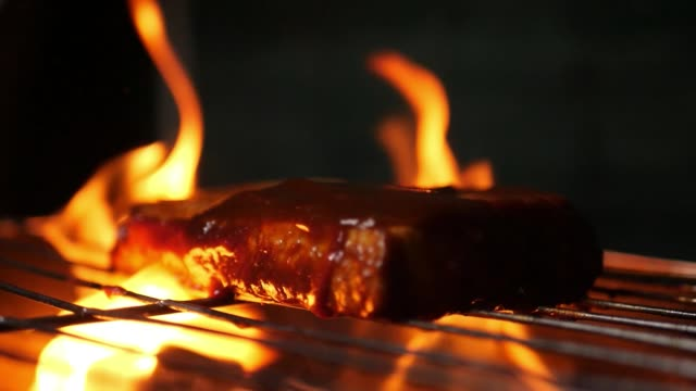 Closeup of a cottage cheese steak being barbecued on a grill with dramatic smoke and fire