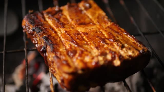 Closeup of a cottage cheese steak being barbecued on a grill with dramatic smoke