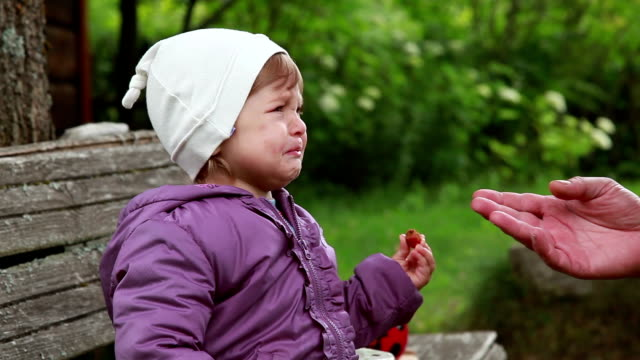 Close-up of a crying baby offering strawberry to her father