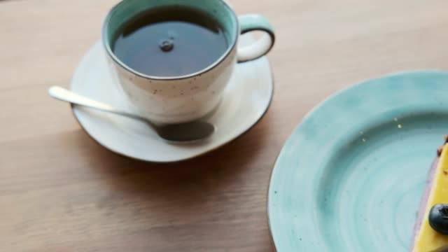pencerenin yanında rahat bir kafede bir masada çay ve yaban mersini cheesecake bir tatlı ile bir fincan yakın çekim. - kek dilimi stok videoları ve detay görüntü çekimi