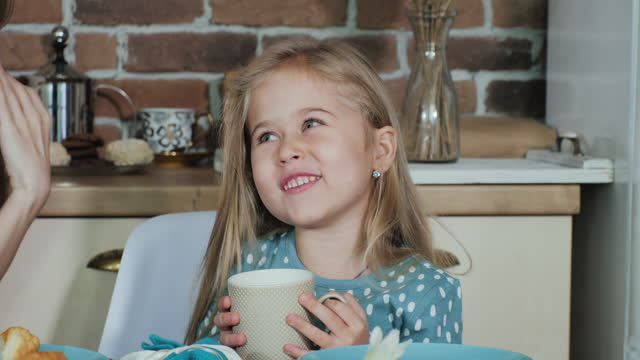 Close-up of a cute funny girl at breakfast. Mom wipes daughter's milk mustache.