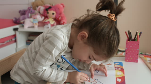 Close-up of a cute little girl looking at camera then backs to coloring video