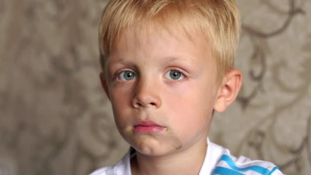 крупным планом лицо грязного маленького мальчика. ребенок пачкается, играя на улице - голодный стоковые видео и кадры b-roll