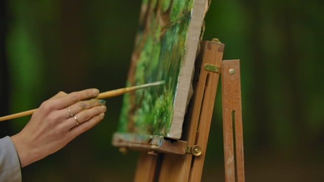 Close-up of a female hand with a brush painting a landscape in the plenar