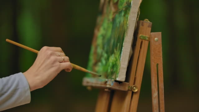 Close-up of a female hand with a brush painting a landscape in the plenar. Finishing touches