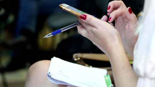 closeup of a female hands holds a pen and typing text message on smartphone sitting video
