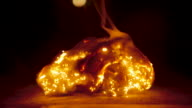 istock Closeup of a fire brightly burning through steel wool and causing it to fall apart 1184864419
