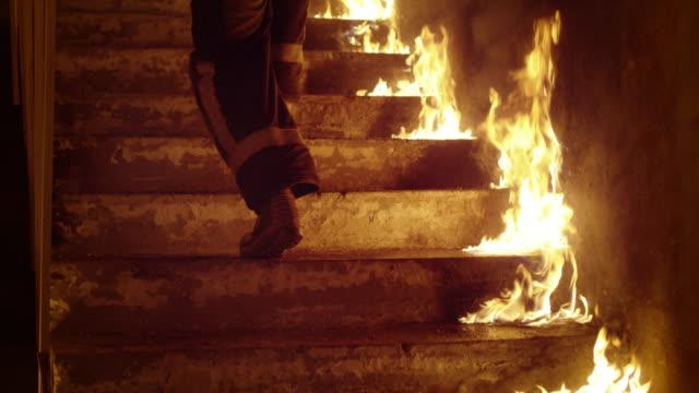 Nahaufnahme der ein Feuerwehrmann Beine brennen Treppe hinauf laufen. Gebäude steht in Flammen, die offene Flammen überall zu sehen sind. Slow-Motion. – Video