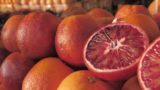 Close-up of a fresh crimpson oranges on fruit market. Boxes full of ripe oranges on farmers market. Organic fruits display in a supermarket. Juicy blood oranges at the greengrocer's stall. Harvest of blood oranges on the counter, one blood orange cut in