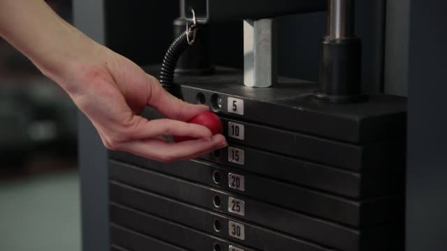 close-up of a girl changing the bar with the weight on the simulator. body-building. the girl goes in for sports at the gym, sets the weight on the simulator - weights stock videos & royalty-free footage