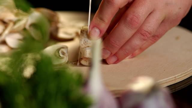 stockvideo's en b-roll-footage met close-up van een meisje snijden paddestoelen aan boord. - kampioenschap