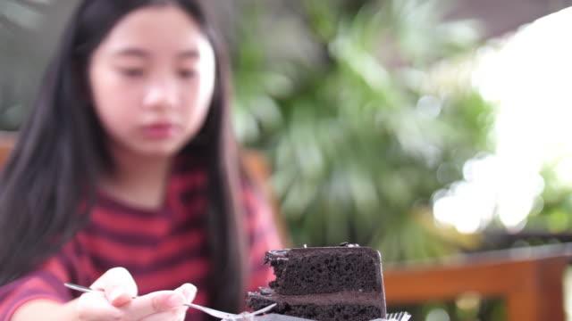 close-up of a girl eating a cake - pieczony filmów i materiałów b-roll