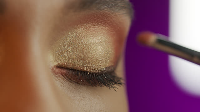 Close-up of a girl eyes, make-up artist applies eyeshadow with a make-up brush. video