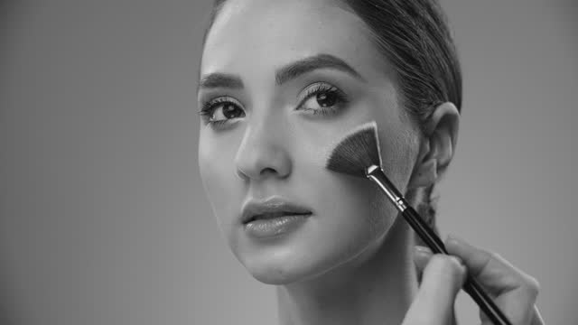 Close-up of a girl face as a highlighter is applied to her cheeks with a make-up brush. Black and white video. video