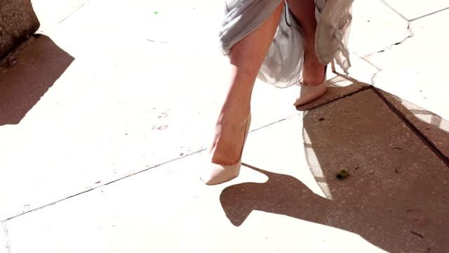 nahaufnahme eines mädchens in einem abendkleid und in high heels zu fuß entlang der straße. - schuhwerk videos stock-videos und b-roll-filmmaterial