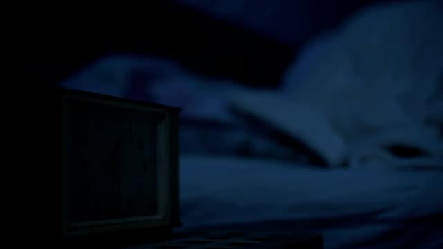 vídeos y material grabado en eventos de stock de primer plano de una chica en pijama acostada en la cama y sin poder dormir mirando un despertador. enfoque variable de horas a chicas. el efecto de la noche americana. - dormitorio habitación