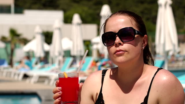 Close-up of a girl in sunglasses drinking a cocktail on a lounger by the pool.