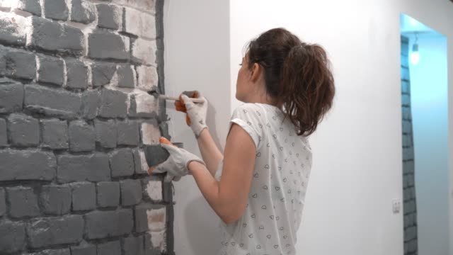 close-up of a girl painting a brick wall in gray using a paint brush. - mattone video stock e b–roll