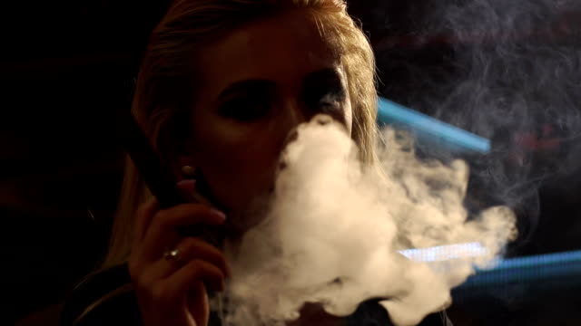 close-up of a girl smoking a cigar, she blows a lot of smoke on the camera. - sigaro video stock e b–roll