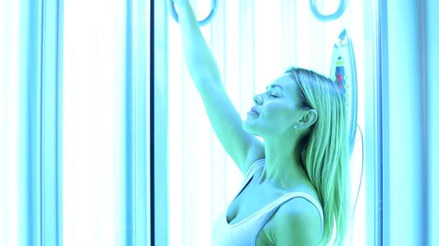 stockvideo's en b-roll-footage met close-up van een meisje met een slanke lichaam zonnebaden in een moderne verticale solarium. - gebruind