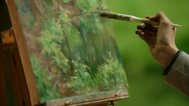 close-up of a girl's palm an artist with a brush doing the blurring touches over her painting - painter stock videos & royalty-free footage