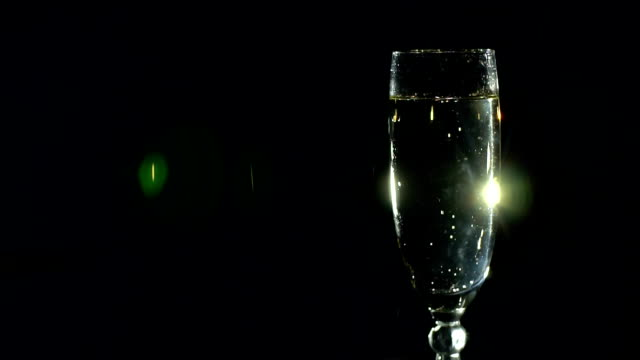 Close-up of a glass of champagne in the dark. video