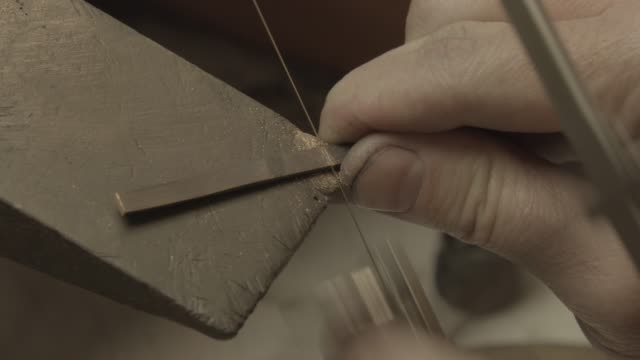 Close-up of a goldsmith sawing a piece of gold video