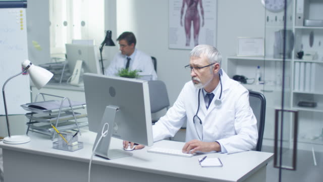 Nahaufnahme von grauen Haaren Senior Arzt und seinem Assistenten arbeiten bei Desktop-Computern. Sitzen in hell beleuchteten Büro. – Video
