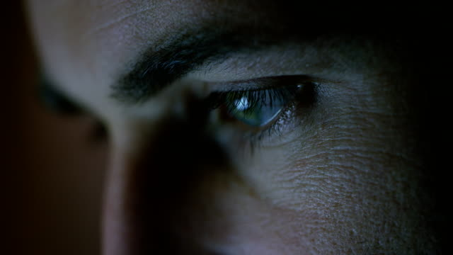 close-up of a green-blue man's eyes with screen reflecting in them. - vicino video stock e b–roll