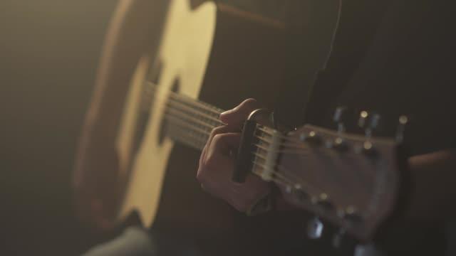 vídeos de stock, filmes e b-roll de close-up de uma pessoa de jogo da guitarra - música acústica