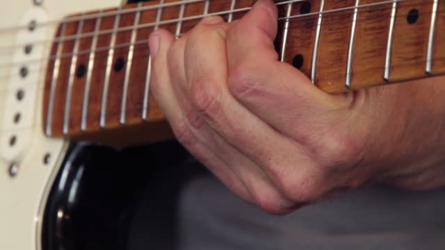 close-up of a guitarist's hand on the guitar fretboard playing showing how to do the bending technique in a solo - inarcare la schiena video stock e b–roll