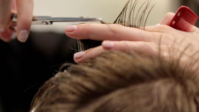 vídeos y material grabado en eventos de stock de primer plano de un peluquero cortando pelo de un joven con tijeras - cabello corto