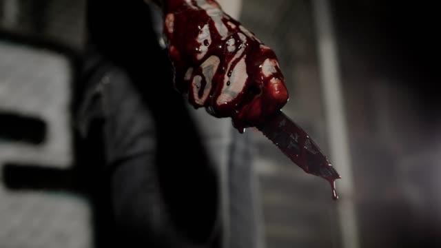 vidéos et rushes de plan rapproché d'une main retenant un couteau sanglant la nuit - lame