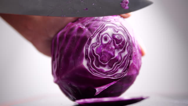 close-up of a hand holding a knife and slicing red cabbage - капустные стоковые видео и кадры b-roll