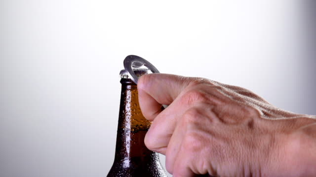 Closeup of a hand opening a bottle of beer in slow motion