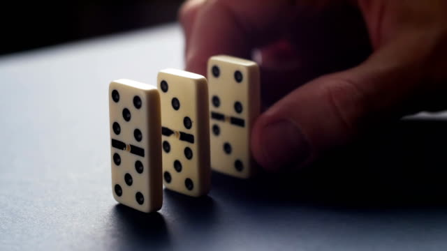 Closeup of a hand putting a domino chain. Domino Effect video