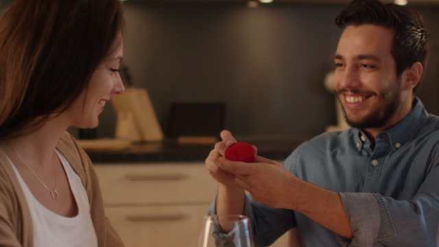 Close-up of a Handsome Young Man Proposing to His Girlfriend. He Opens Ring Box for Her. This Happy Fact Takes Place in the Kitchen. - vídeo