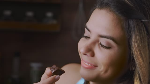 close-up of a happy hispanic woman eating indulgence chocolate in a rustic kitchen - cioccolato video stock e b–roll