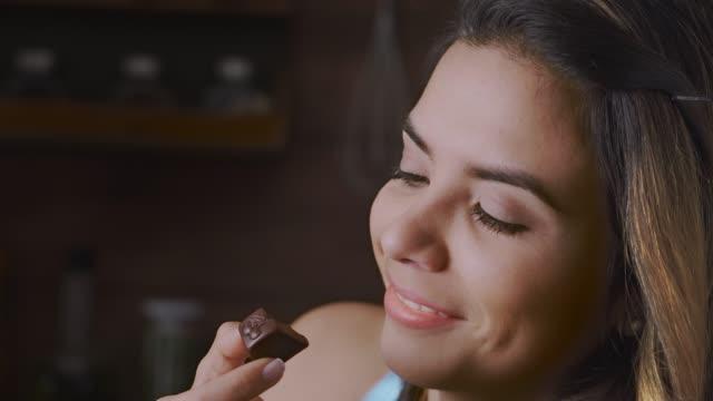 rustik bir mutfakta hoşgörü çikolata yeme mutlu bir ispanyol kadın yakın çekim - chocolate stok videoları ve detay görüntü çekimi