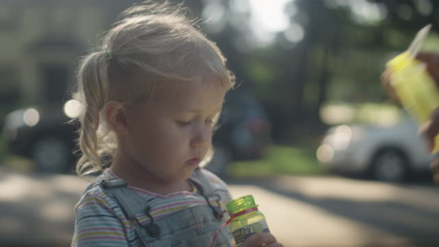 Close-up of a little blonde girl and her father blowing bubbles on a sunny day Close-up of a little blonde girl and her father blowing bubbles on a sunny day pigtails stock videos & royalty-free footage