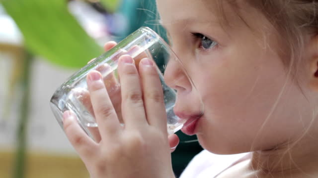 close-up of a little cute girl drinking pure water from a glass - напиток стоковые видео и кадры b-roll