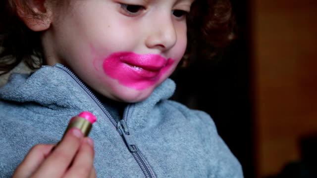 nahaufnahme eines kleinen mädchens, malen ihre lippen mit lippenstift - lippenstift stock-videos und b-roll-filmmaterial