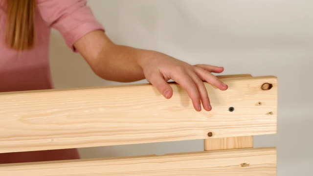 Close-up of a little girl's hand on a wooden bench in a room with a white wall.