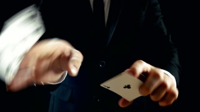 Close-up of a Magician's Hands Performing Card Trick. Throwing and Catching Cards Deck in the Air. Background is Black. Slow Motion. video